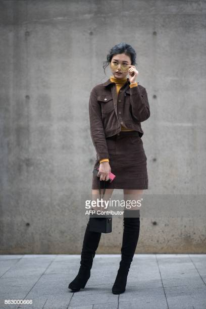 An attendee poses for photographers during Seoul Fashion Week at Dongdaemun Design Plaza in Seoul on October 19 2017 For Seoul's flamboyant followers...