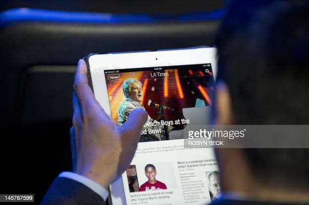 An attendee reads a Los Angeles Times newspaper article using the Flipboard app on an iPad as he waits for the start of the Nintendo E3 2012 media...