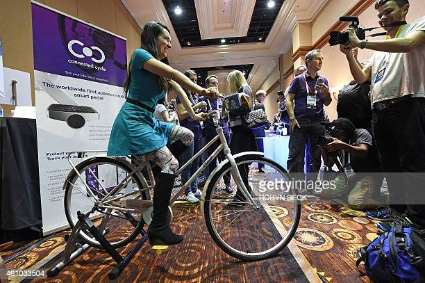 An attendee rides a bicycle equipped with a yellow Connected Cycle smart pedal during media preview event at the 2015 Consumer Electronics Show...
