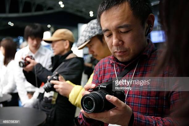 An attendee right inspects a Nikon Corp D3300 digital single lens reflex camera at the CP Camera and Photo Imaging Show in Yokohama Kanagawa...