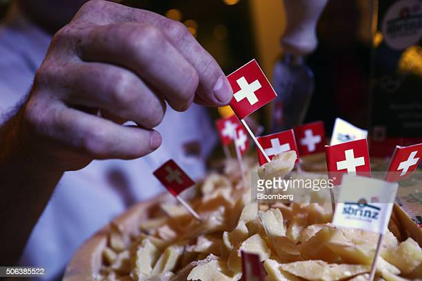 An attendee samples Swiss cheese using a cocktail stick with a mini Swiss national flag on it during a closing day buffet at the World Economic Forum...