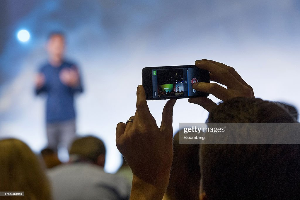 An attendee shoots video on a smart phone using the new video feature of Instagram as Kevin Systrom, chief executive officer and founder of Instagram Inc., speaks during an event at Facebook Inc. headquarters in Menlo Park, California, U.S., on Thursday, June 20, 2013. Facebook Inc., operator of the largest social network, plans to unveil video-sharing tools, bringing its Instagram into closer competition with Twitter Inc., a person with knowledge of the matter said. Photographer: David Paul Morris/Bloomberg via Getty Images