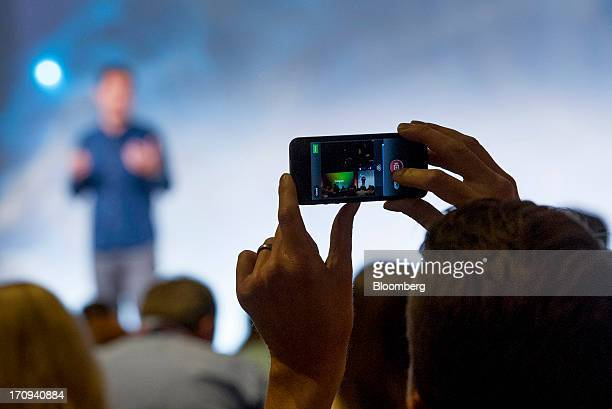 An attendee shoots video on a smart phone using the new video feature of Instagram as Kevin Systrom chief executive officer and founder of Instagram...