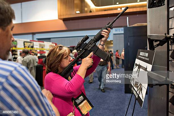 An attendee sights a rifle in the ArmaLite Inc booth on the exhibition floor of the 144th National Rifle Association Annual Meetings and Exhibits at...