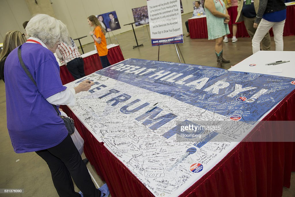 An attendee signs a 'Defeat Hillary Vote Trump' banner at the Trump campaign booth during the 2016 Texas Republican Convention in Dallas Texas US on...