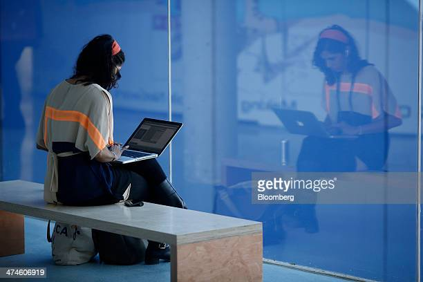 An attendee sits and works on a laptop computer on the opening day of the Mobile World Congress in Barcelona Spain on Monday Feb 24 2014 Top...
