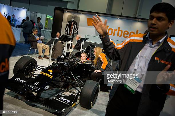 An attendee sits in a race car built with graphene nanotechnology is displayed at the Vorbeck Materials Corp booth during the 2015 Consumer...