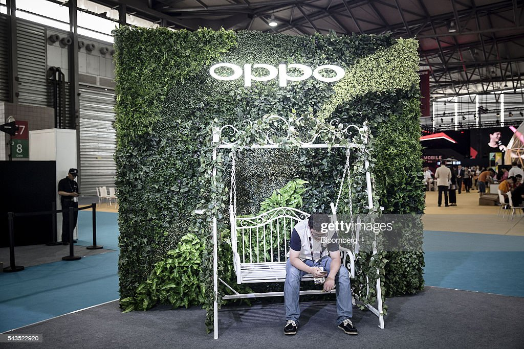 An attendee sits in front of signage for smartphone maker Oppo at the Mobile World Congress Shanghai in Shanghai, China, on Wednesday, June 29, 2016. The exhibition runs until July 1. Photographer: Qilai Shen/Bloomberg via Getty Images