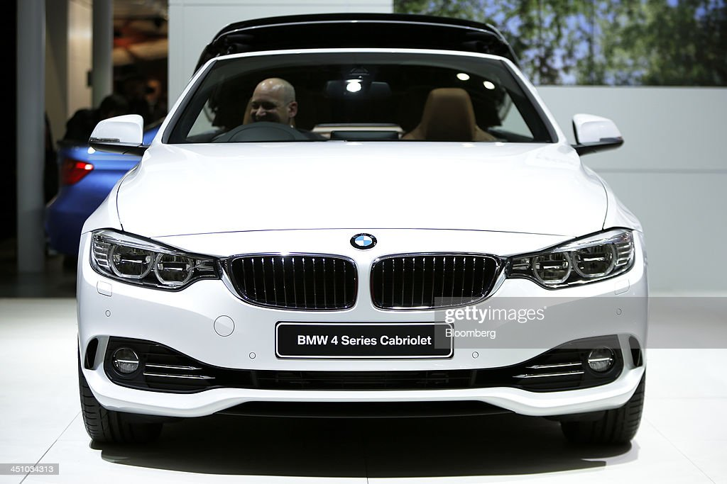 An attendee sits in the driver's seat of a Bayerische Motoren Werke AG (BMW) 4 Series Cabriolet vehicle at the 43rd Tokyo Motor Show 2013 in Tokyo, Japan, on Thursday, Nov. 21, 2013. The autoshow will be open to the public from Nov. 23 to Dec. 1 at the Tokyo International Exhibition Center, also known as the Tokyo Big Sight. Photographer: Kiyoshi Ota/Bloomberg via Getty Images