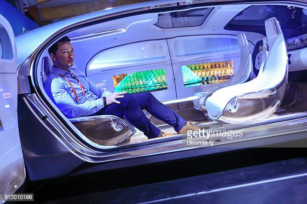 An attendee sits inside the MercedesBenz AG F015 concept car produced by Daimler AG at the Mobile World Congress in Barcelona Spain on Wednesday Feb...