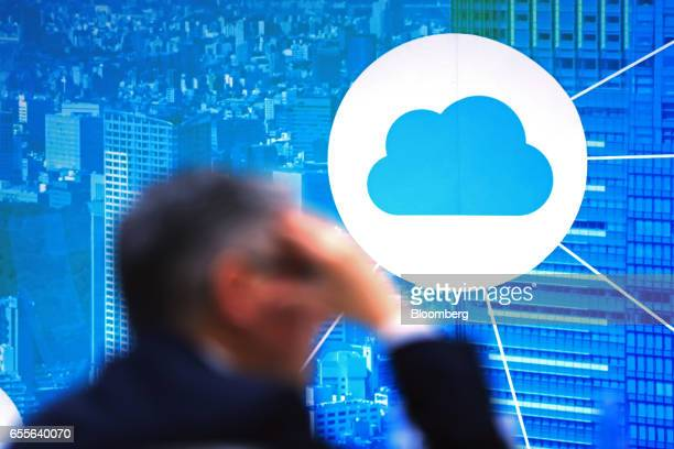 An attendee sits near an illuminated display advertising iCloud technology at the CeBIT 2017 tech fair in Hannover Germany on Monday March 20 2017...