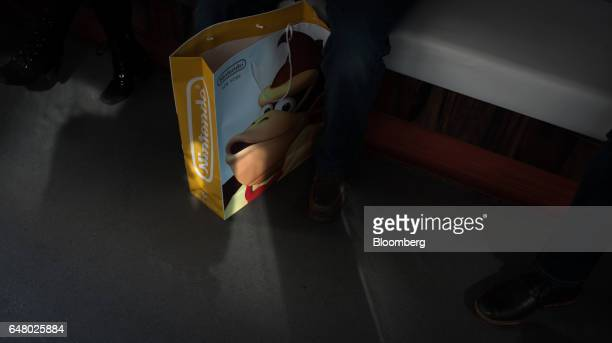 An attendee sits with a Nintendo Co bag inside the company's bus during the Nintendo Switch game console launch event in New York US on Friday March...