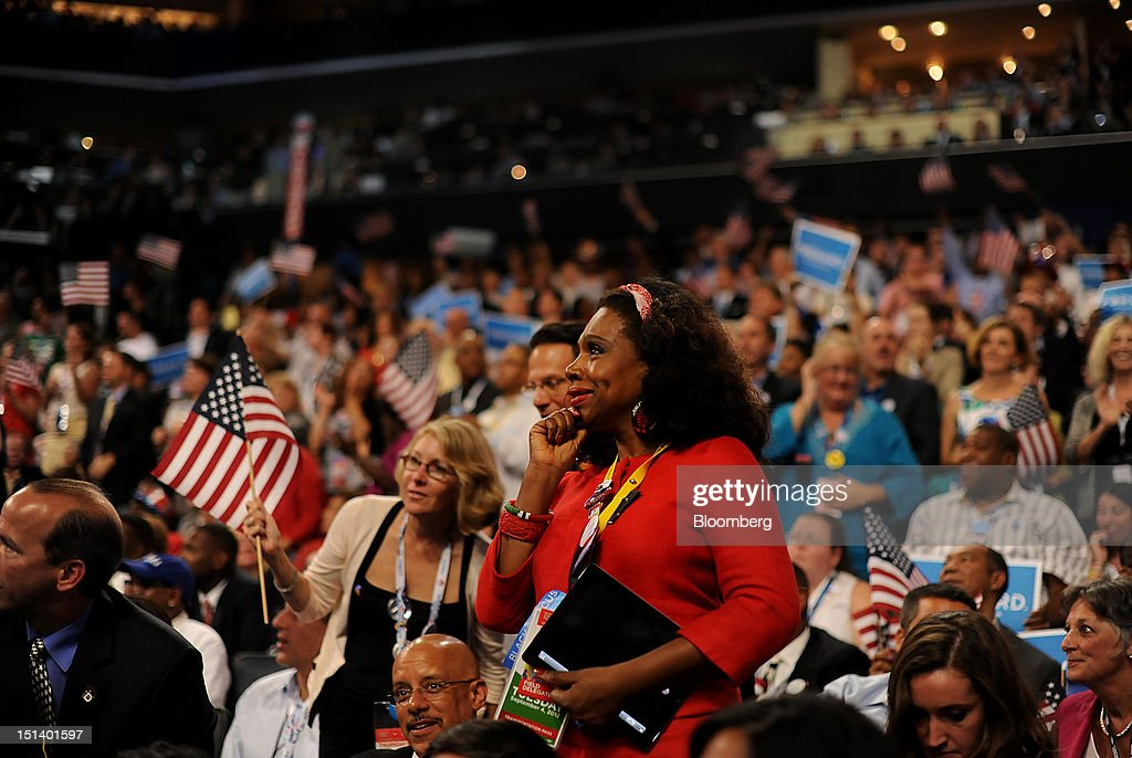 An attendee smiles while listening to U.S. President Barack Obama, unseen, speak during day three of the Democratic National Convention (DNC) in Charlotte, North Carolina, U.S., on Thursday, Sept. 6, 2012. President Barack Obama's prime-time nomination acceptance speech tonight at the DNC is aimed at convincing voters that a slow economic recovery will accelerate if they give him a second term. Photographer: Daniel Acker/Bloomberg via Getty Images