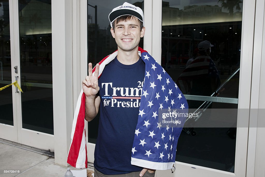 An attendee stands for a photograph while waiting in line before the start of a campaign event for Donald Trump, presumptive Republican presidential nominee, not pictured, in San Diego, California, U.S., on Friday, May 27, 2016. Trump said he would rescind 'job-destroying' Obama administration environmental actions within 100 days of taking office and cancel a landmark international climate deal reached last year in Paris. Photographer: Patrick T. Fallon/Bloomberg via Getty Images