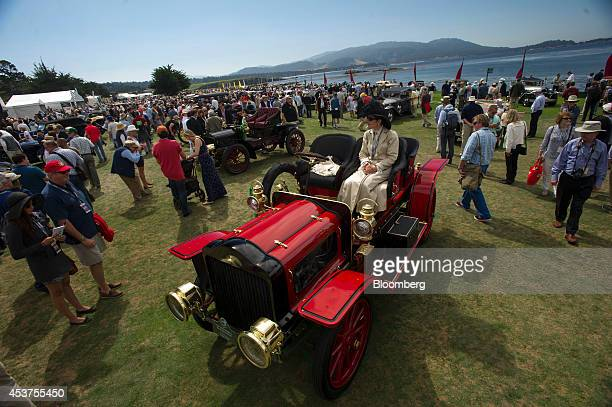 An attendee takes a break in her automobile during the 2014 Pebble Beach Concours d'Elegance in Pebble Beach California US on Sunday Aug 17 2014 The...