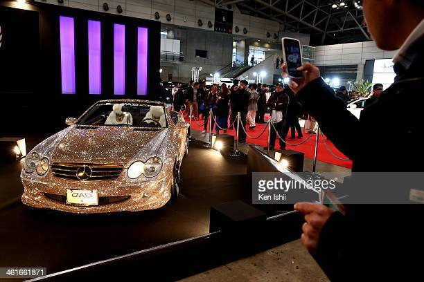 An attendee takes a photo of a customized Daimler AG MercedesBenz vehicle decorated with Swarovski crystals is displayed at the Tokyo Auto Salon 2014...
