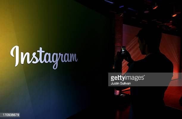 An attendee takes a photo of the instagram logo during a press event at Facebook headquarters on June 20 2013 in Menlo Park California Facebook...