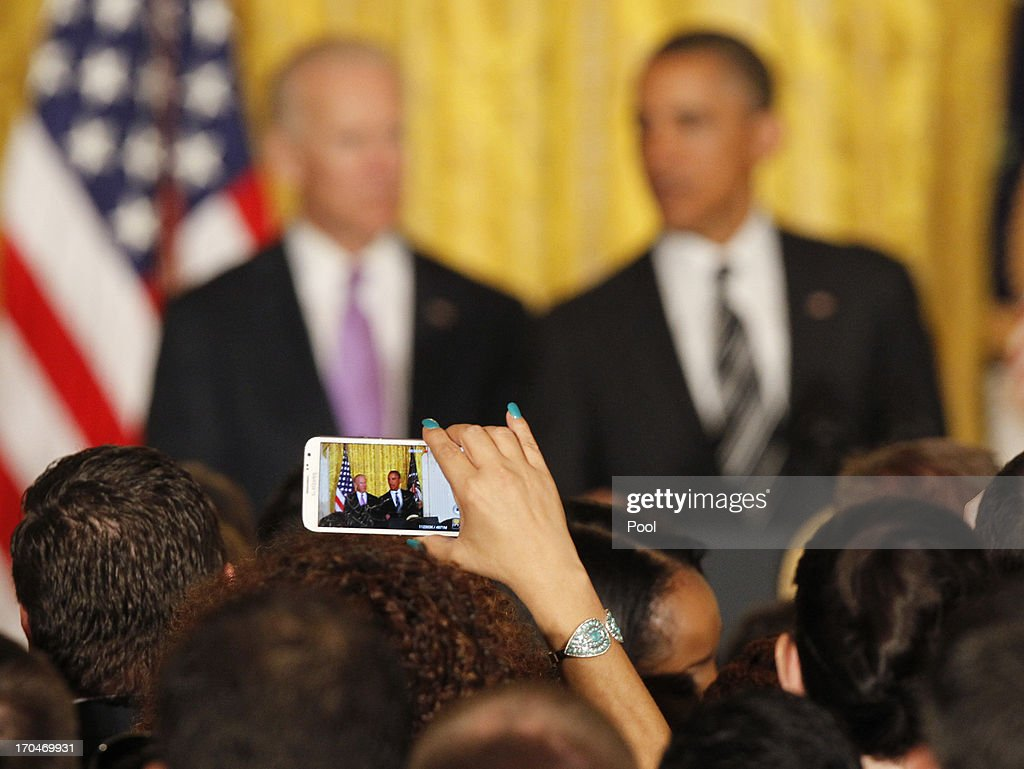 An attendee takes a photo of U.S. President <a gi-track='captionPersonalityLinkClicked' href=/galleries/search?phrase=Barack+Obama&family=editorial&specificpeople=203260 ng-click='$event.stopPropagation()'>Barack Obama</a> and Vice President Joe Biden as they take part in the LGBT Pride Month celebration on June 13, 2013 in the East Room at the White House in Washington DC.