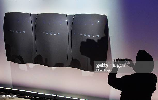 An attendee takes a photograph during the unveiling of Tesla Motors Inc's 'Powerwall' at an event in Hawthorne California US on Thursday April 30...