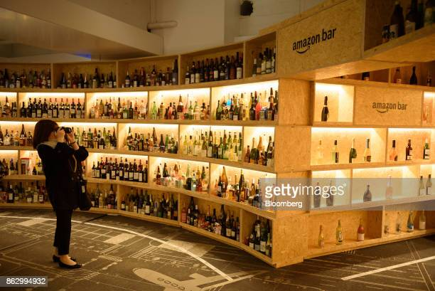 An attendee takes a photograph inside the Amazon Bar operated by Amazon Japan KK during a media preview in Tokyo Japan on Thursday Oct 19 2017 For 10...