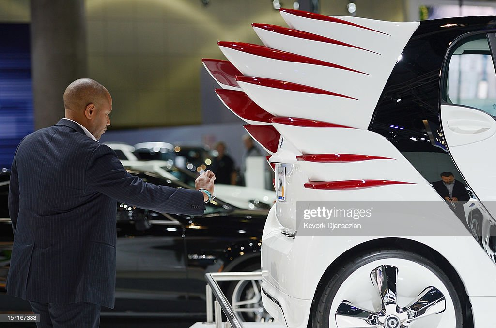 An attendee takes a photograph of a Daimler AG Smart car during the Los Angeles Auto show on November 29, 2012 in Los Angeles, California. The LA Auto Show opens to the public on November 30 and runs through December 9.