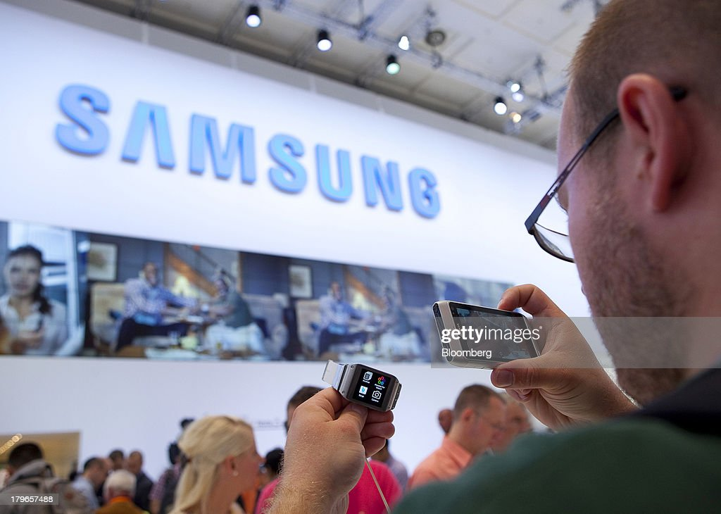 An attendee takes a photograph of a Galaxy Gear smart watch device, manufactured by Samsung Electronics Co., at the IFA consumer electronics show in Berlin, Germany, on Friday, Sept. 6, 2013. Global smartphone revenue will rise 22 percent in 2013, or nearly half the pace of an expected 41 percent gain in shipments, amid falling prices, according to UBS. Photographer: Krisztian Bocsi/Bloomberg via Getty Images