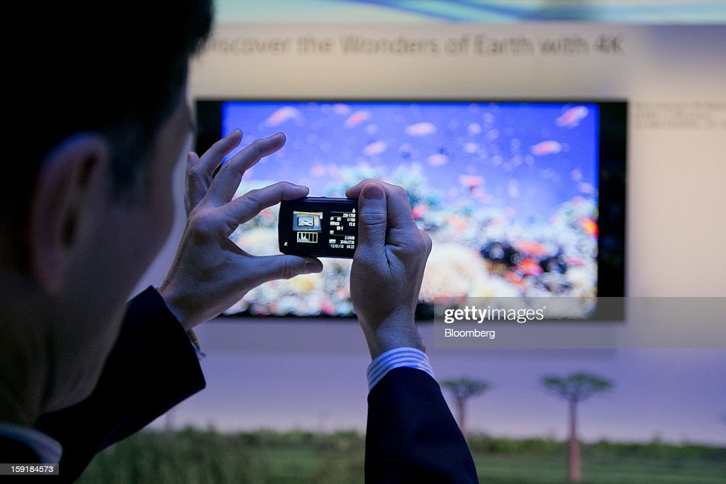 An attendee takes a photograph of a Sony Corp. 65-inch 4K LED television during the 2013 Consumer Electronics Show in Las Vegas, Nevada, U.S., on Wednesday, Jan. 9, 2013. Sony Corp. is enabling its Bravia TVs, Handycam camcorders and Xperia phones to communicate with each other as Chief Executive Officer Kazuo Hirai tries to end four years of losses. Photographer: Andrew Harrer/Bloomberg via Getty Images