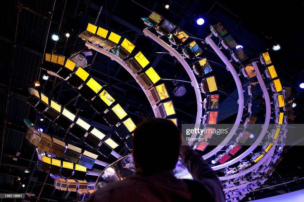 An attendee takes a photograph of laptop computers arranged in a display at the 2013 Consumer Electronics Show in Las Vegas, Nevada, U.S., on Wednesday, Jan. 9, 2013. The 2013 CES trade show, which runs until Jan. 11, is the world's largest annual innovation event that offers an array of entrepreneur focused exhibits, events and conference sessions for technology entrepreneurs. Photographer: David Paul Morris/Bloomberg via Getty Images