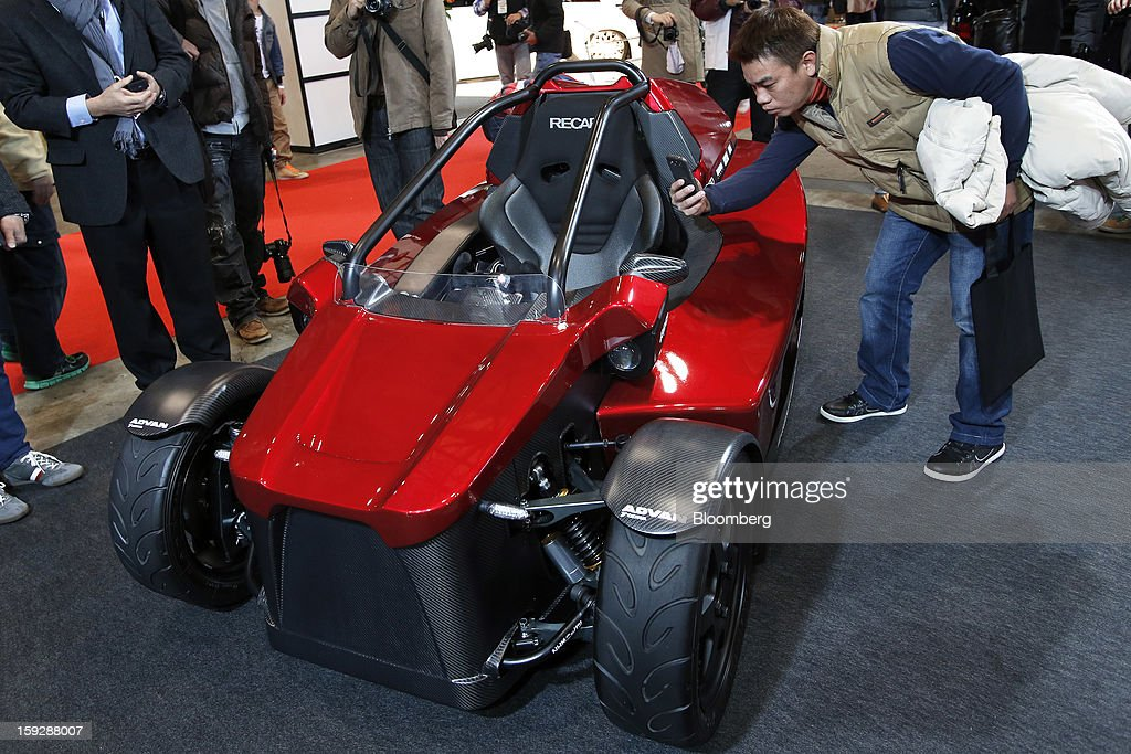 An attendee takes a photograph of Toyota Engineering Society's (TES) Minute-S one-rider, three-wheeled hybrid vehicle displayed at the Tokyo Auto Salon 2013 at Makuhari Messe in Chiba, Japan, on Friday, Jan. 11, 2013. The Tokyo Auto Salon runs until Jan. 13. Photographer: Kiyoshi Ota/Bloomberg via Getty Images