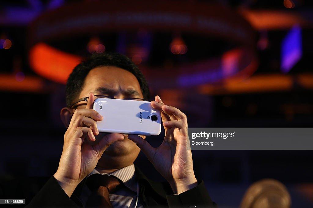 An attendee takes a photograph using a Samsung Electronics Co. mobile device at the 22nd World Energy Congress (WEC) in Daegu, South Korea, on Monday, Oct. 14, 2013. The WEC, a global conference on the energy market, will run until Oct. 17. Photographer: SeongJoon Cho/Bloomberg via Getty Images