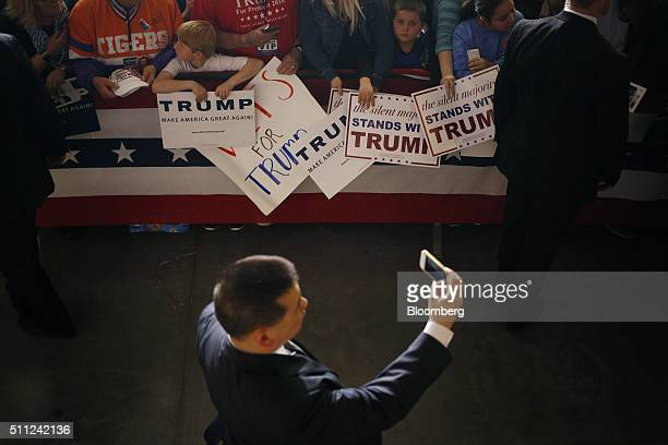 An attendee takes a photograph using a smartphone as attendees hold campaign signs supporting Donald Trump president and chief executive of Trump...