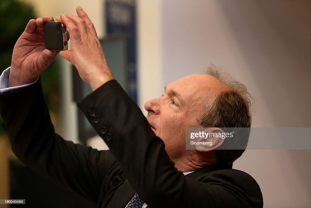 An attendee takes a photograph using his Apple Inc. iPhone inside the Congress Center on day three of the World Economic Forum (WEF) in Davos, Switzerland, on Friday, Jan. 25, 2013. World leaders, influential executives, bankers and policy makers attend the 43rd annual meeting of the World Economic Forum in Davos, the five day event runs from Jan. 23-27. Photographer: Chris Ratcliffe/Bloomberg via Getty Images