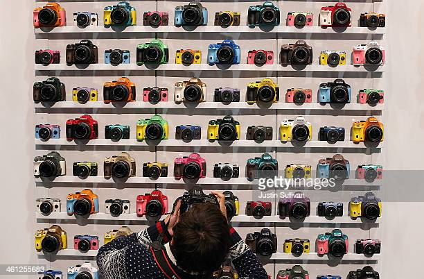 An attendee takes a picture of a display of Pentax cameras in the Ricoh booth at the 2014 International CES at the Las Vegas Convention Center on...