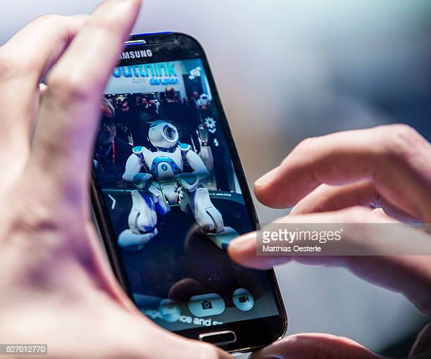An attendee takes a picture of the robot 'WATSON' from IBM during the second day of the annual Mobile World Congress one of the most important events...