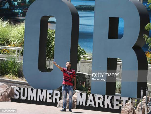 An attendee takes a selfie photograph with signage outside the Outdoor Retailer Summer Market Show in Salt Lake City Utah US on Saturday July 29 2017...