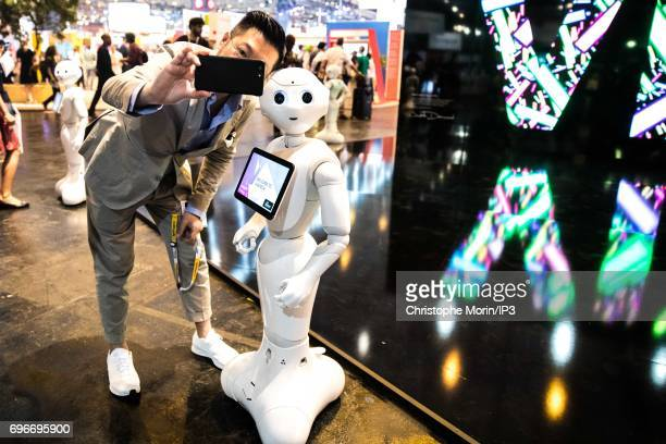 An attendee takes a selfie with a Pepper humanoid robot manufactured by SoftBank Group Corp during Viva Technology at Parc des Expositions Porte de...