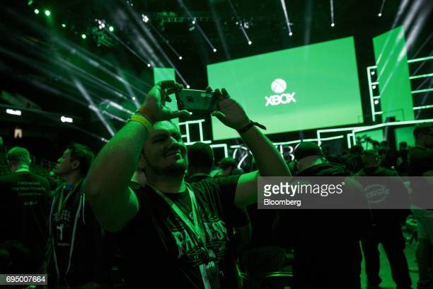 An attendee takes photographs following the Microsoft Corp Xbox One X reveal event ahead of the E3 Electronic Entertainment Expo in Los Angeles...
