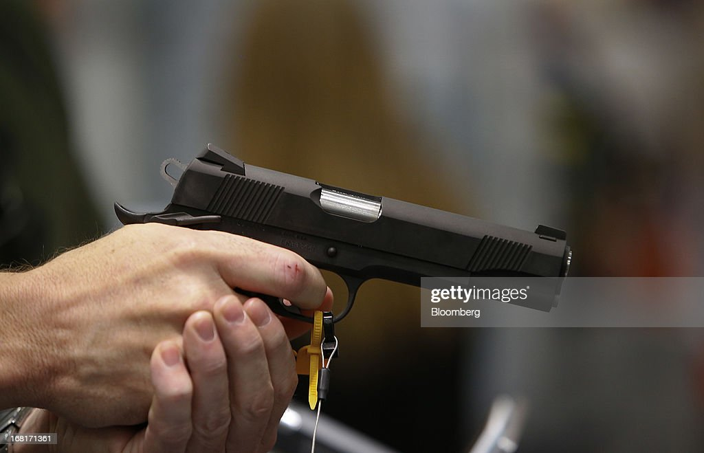 An attendee tests a Colt Defense LLC handgun during the 2013 National Rifle Association (NRA) Annual Meetings & Exhibits at the George R. Brown Convention Center in Houston, Texas, U.S., on Saturday, May 4, 2013. After the U.S. Senate defeated a proposed expansion of background checks on gun purchases, the NRA's annual conference has a celebratory atmosphere. Yet as the festivities began, gun-control advocates swarmed town halls, organizing petitions and buying local ads to pressure senators from Alaska to New Hampshire to reconsider the measure that failed by six votes on April 17. Photographer: Aaron M. Sprecher/Bloomberg via Getty Images