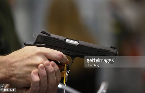 An attendee tests a Colt Defense LLC handgun during the 2013 National Rifle Association Annual Meetings Exhibits at the George R Brown Convention...