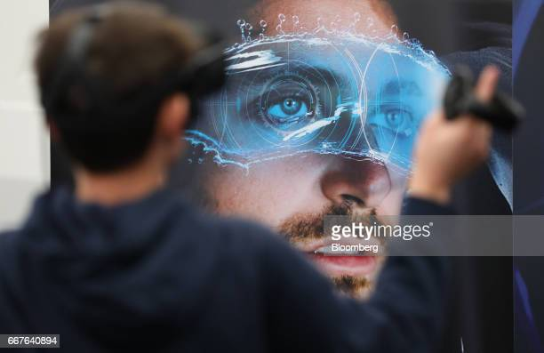 An attendee tests an interactive virtual reality headset on the Advanced Micro Devices Inc stand at the Virtual Reality World Congress in Bristol UK...