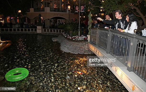An attendee tosses a coin into The Grove's Dancing Fountain during ''A Taste of Italy'' on January 28 2010 in Los Angeles California The event was...