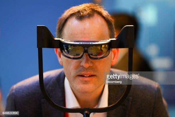 An attendee tries a pair of ODG R9 smartglasses manufactured by Osterhout Group Inc on the Qualcomm Inc stand on the third day of Mobile World...