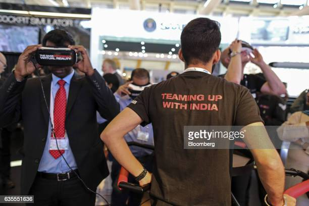 An attendee tries a virtual reality headset at the SAAB AB booth during the Aero India air show at Air Force Station Yelahanka in Bengaluru India on...