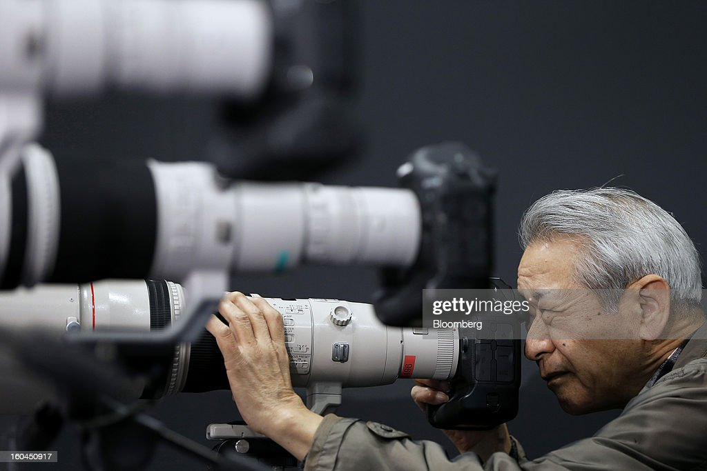 An attendee tries out a Canon Inc. EOS-1D X digital single lens reflex (DSLR) camera mounted with an EF 800mm f/5.6L IS USM super telephoto lens at the CP+ Camera and Photo Imaging Show in Yokohama City, Japan, on Thursday, Jan. 31, 2013. The CP+ Camera and Photo Imaging Show runs from Jan. 31 to Feb. 3. Photographer: Kiyoshi Ota/Bloomberg via Getty Images