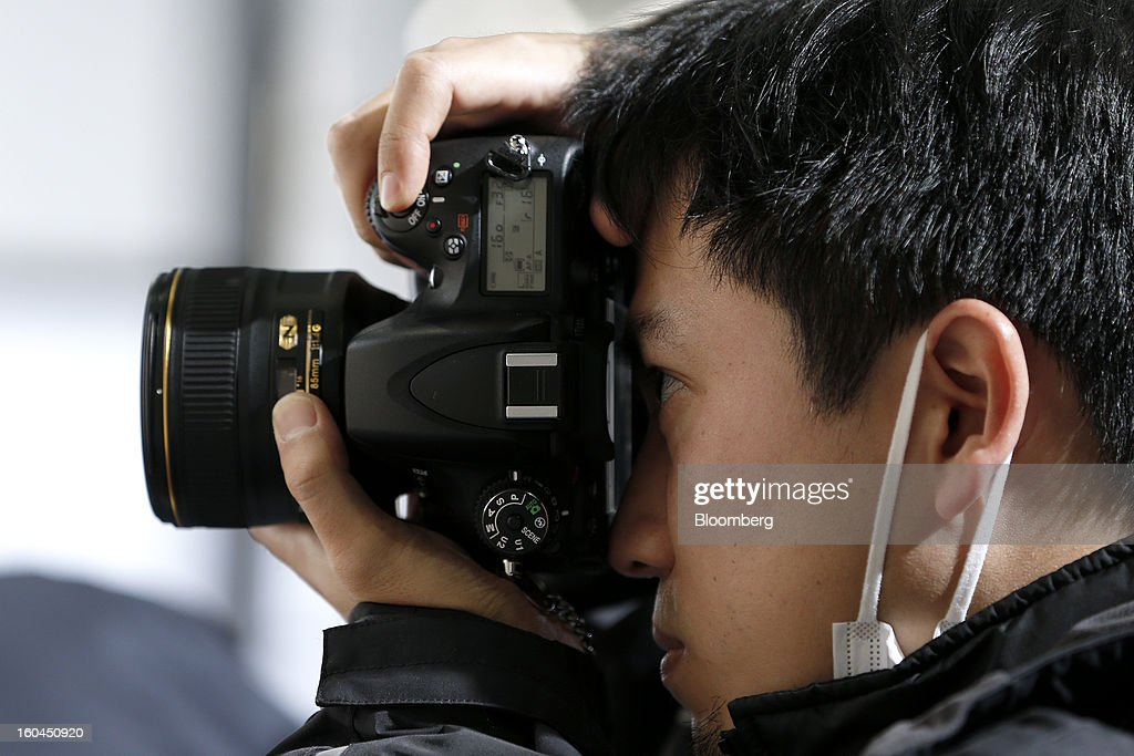 An attendee tries out a Nikon Corp. D600 digital single lens reflex (DSLR) camera at the CP+ Camera and Photo Imaging Show in Yokohama City, Japan, on Thursday, Jan. 31, 2013. The CP+ Camera and Photo Imaging Show runs from Jan. 31 to Feb. 3. Photographer: Kiyoshi Ota/Bloomberg via Getty Images