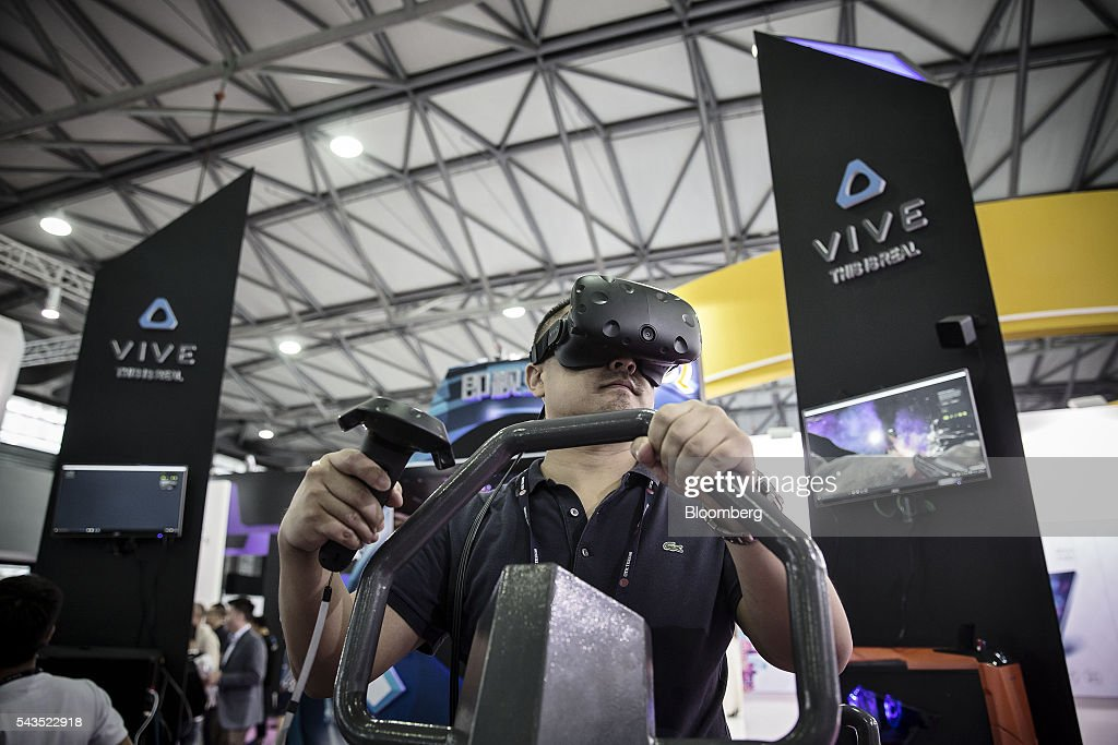 An attendee tries out a virtual reality (VR) game on HTC Corp.'s Vive headset at the Mobile World Congress Shanghai in Shanghai, China, on Wednesday, June 29, 2016. The exhibition runs until July 1. Photographer: Qilai Shen/Bloomberg via Getty Images