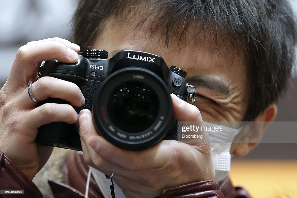 An attendee tries out Panasonic Corp.'s Lumix DMC-GH3 mirrorless digital camera at the CP+ Camera and Photo Imaging Show in Yokohama City, Japan, on Thursday, Jan. 31, 2013. Panasonic, Japan's second-biggest television maker, reported an unexpected third-quarter profit because of a weaker yen and restructuring efforts. Photographer: Kiyoshi Ota/Bloomberg via Getty Images