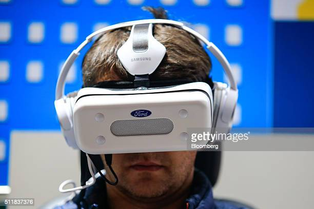An attendee uses a Gear VR headset manufactured by Samsung Electronics Co on the Ford Motors Co stand at the Mobile World Congress in Barcelona Spain...