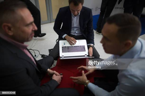 An attendee uses a laptop computer while others network between working sessions at the CrytoSpace conference in Moscow Russia on Friday Dec 8 2017...