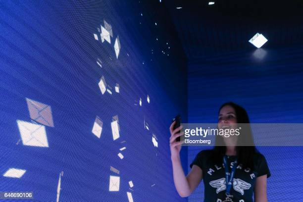 An attendee uses a mobile device beside a digital display of flying envelopes on the MessageBird stand on the third day of Mobile World Congress in...